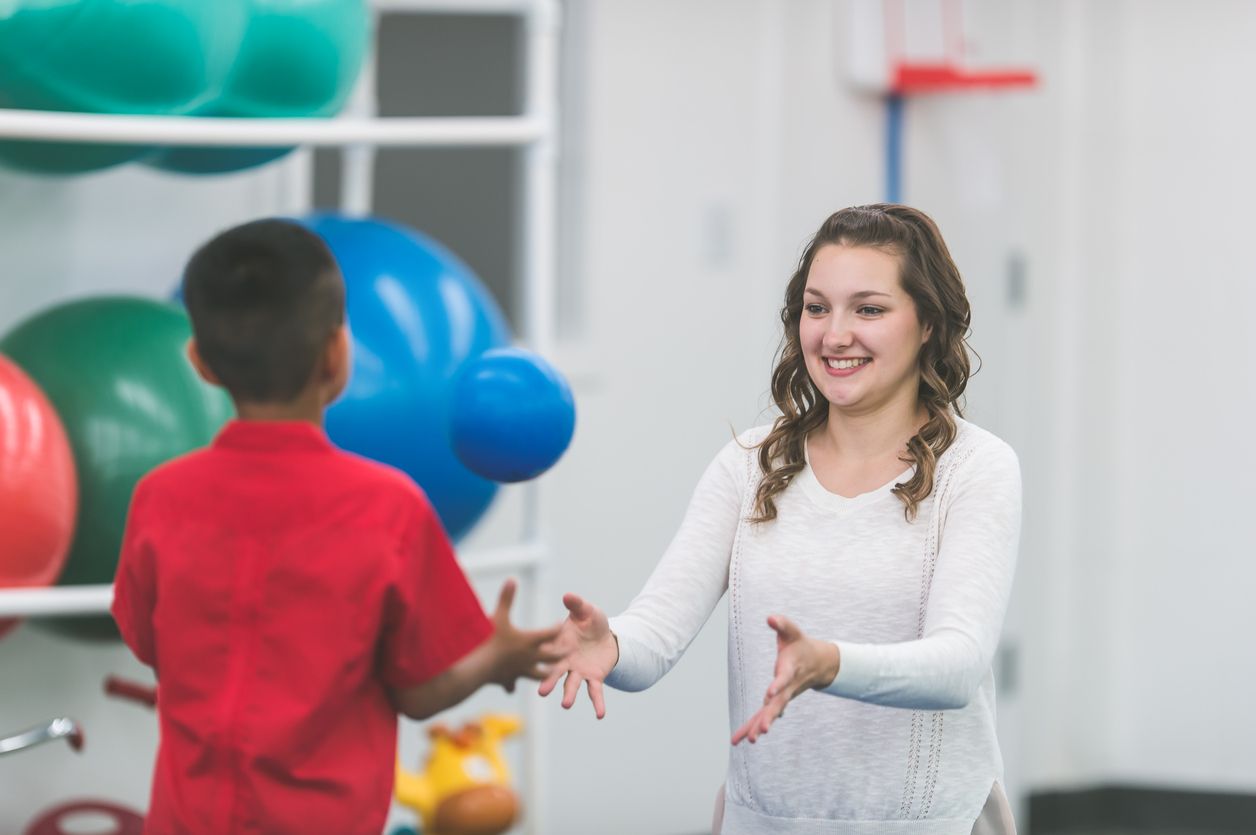 A female physical therapist doing rehabilitation with a child patient. She is working on coordination by throwing a ball to the patient.